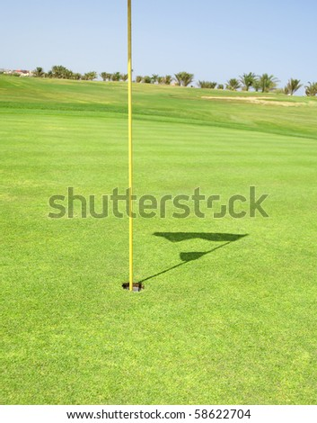Closeup detail of a golf flag in the hole on a course green - stock photo