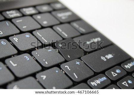 closeup detail of a laptop keyboard with one odd damaged key button