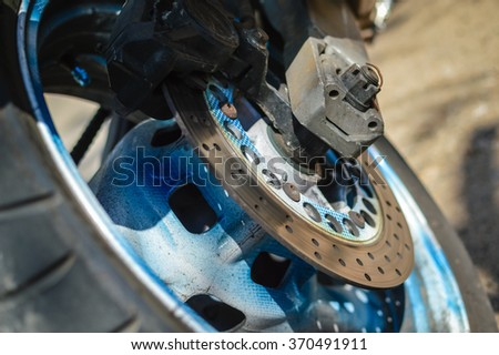 Closeup detail of a motorcycle's back wheel and brake disc