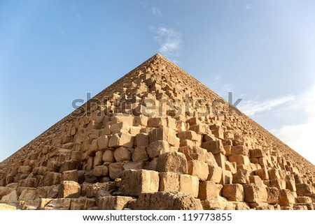 Closeup detail of a Pyramid, Giza, Egypt, against blue sky. The Great Pyramid of Giza is the only remaining of the original Seven Wonders of the world. - stock photo