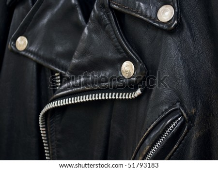 closeup detail of a vintage black leather biker jacket, selective focus on foreground