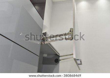 Closeup detail of an actuator hinge on door of a kitchen cupboard - stock photo