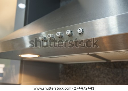Closeup detail of buttons on metal cooker hood extractor fan with spotlight in luxury kitchen - stock photo