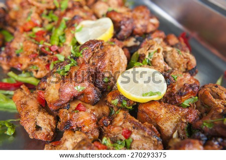 Closeup detail of chicken tikka tandoori pieces at an indian restaurant buffet - stock photo
