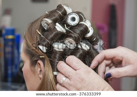 Closeup detail of female womans hair styling being styled at hairdresser salon