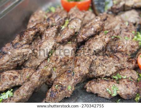 Closeup detail of grilled lamb kofta meat on display at an oriental restaurant buffet - stock photo