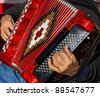 Closeup detail of hands playing a red accordion instrument. - stock photo