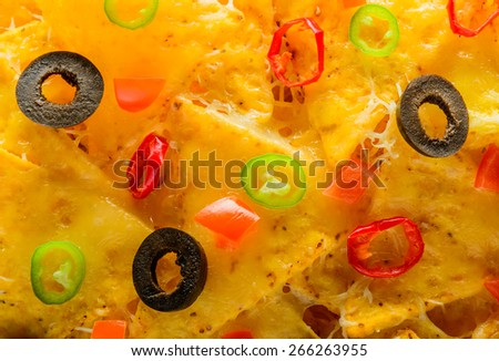 closeup detail of nacho tortilla chips with olives and chili peppers - stock photo