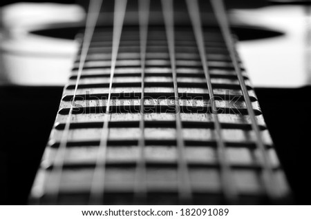 Closeup detail of steel guitar strings and frets for making music - stock photo