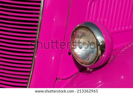 Closeup detail of the headlight of an antique car painted pink - stock photo
