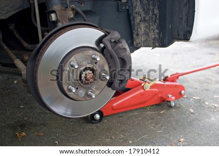 Closeup detail of the wheel assembly on a modern automobile.  The rim is removed showing the front rotor and caliper. - stock photo
