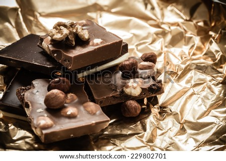 Closeup different sorts chocolate pieces and hazelnuts. Variety of chocolates on golden foil wrapping. - stock photo
