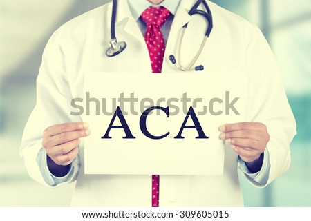 Closeup doctor hands holding white card sign with ACA (or AFFORDABLE CARE ACT)  text message isolated on hospital clinic office background. Retro instagram style filter image - stock photo