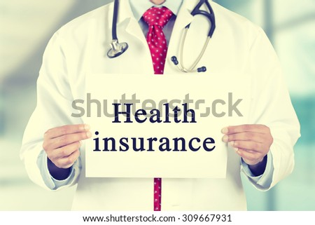 Closeup doctor hands holding white card sign with health insurance text message isolated on hospital clinic office background. Retro instagram style filter image - stock photo