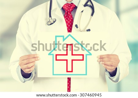 Closeup doctor hands holding white paper house with red cross sign isolated on hospital clinic office background. Retro instagram style filter image - stock photo