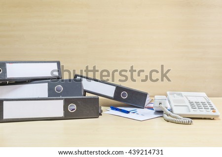 Closeup document file and white phone and work paper in hard work concept on blurred wooden desk and wall textured background in the meeting room under window light - stock photo