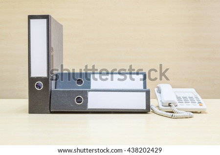 Closeup document file and white phone , office phone on blurred wooden desk and wall textured background in the meeting room under window light - stock photo