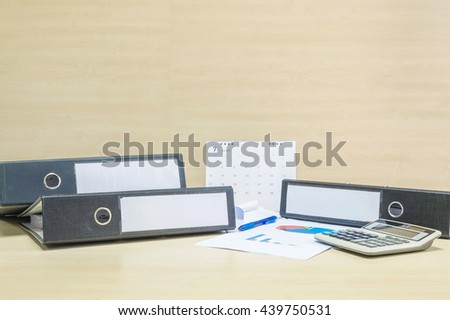 Closeup document file and work paper and calculator in hard work concept on blurred wooden desk and wall textured background in the meeting room under window light - stock photo