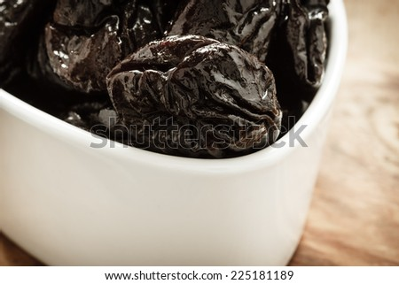 Closeup dried plums prunes fruits  in white bowl on wooden rustic table background - stock photo