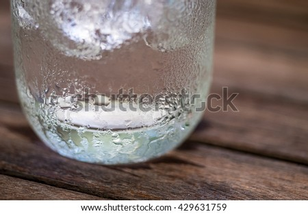 closeup drop or drip on tumbler or glass on wooden table with ice - stock photo