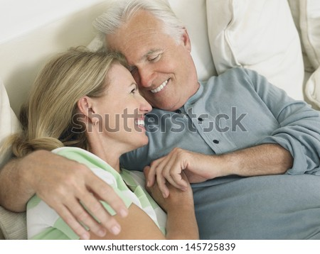 Closeup elevated view of a happy middle aged couple embracing in bed - stock photo