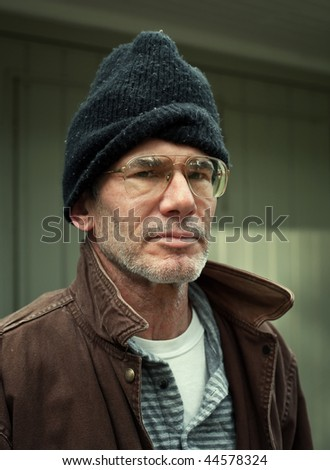Closeup environmental portrait of an older homeless man looking straight at the camera, looking serious. - stock photo