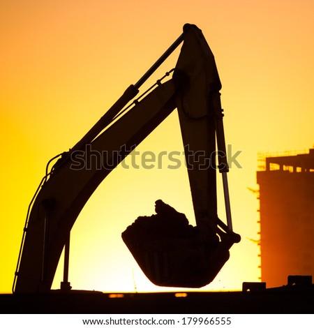 Closeup excavator at sunset - stock photo