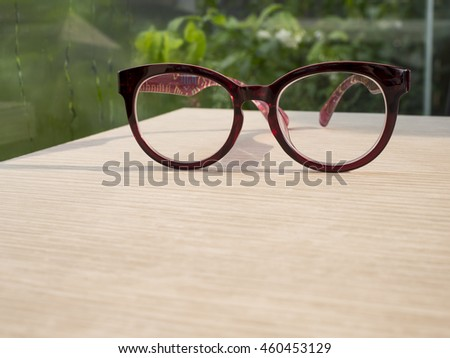 Closeup eye glasses on wood table with green plant background in the coffee shop