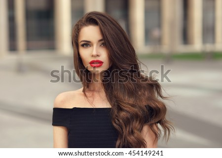 Closeup face fashion portrait of young beautiful pretty stylish girl with long curly brunette hair and red lips posing in city - stock photo