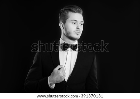 Closeup face of a fashion young businessman in black suit casual poses at studio - stock photo