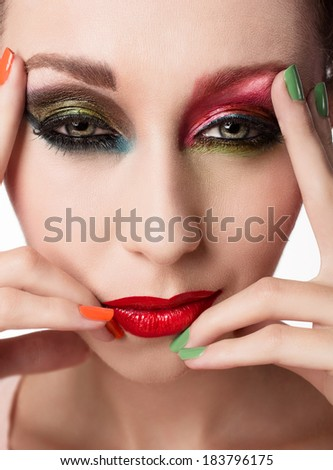 Closeup face of a woman deciding on makeup options: beautiful red lips and artistic eye shadow  - studio shot of bright fashion makeup