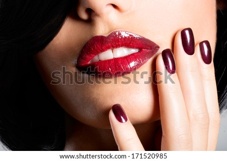 Closeup face of a woman with beautiful sexy red lips and dark nails - studio - stock photo