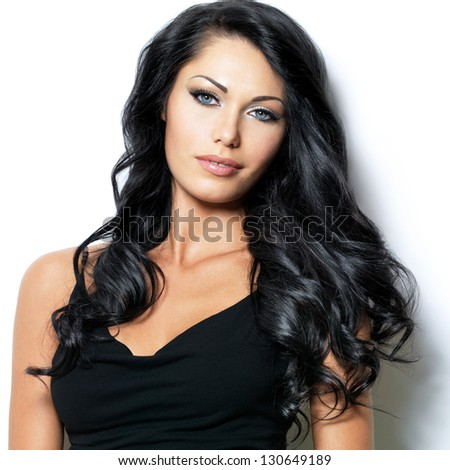 Closeup face of beautiful woman with long black curly hairs at studio - stock photo