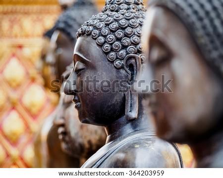 Closeup face of black Buddha statue - stock photo