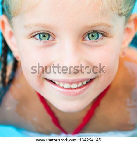 Closeup face of Smiling little girl in swimming pool - stock photo