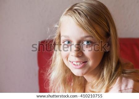 Closeup face portrait of beautiful blond smiling Caucasian girl - stock photo