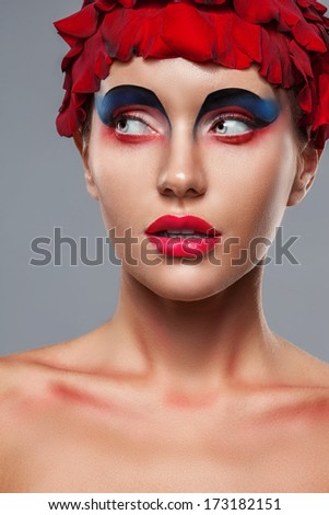 closeup face portrait of woman with creative makeup and rose petals on head - stock photo