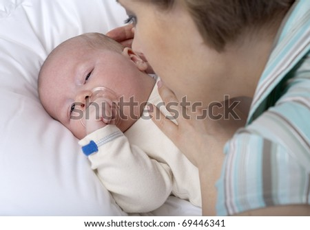 Closeup faces of happy mother with cute newborn baby