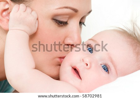 Closeup faces of young happy mother with cute newborn baby - stock photo
