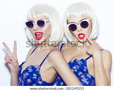 Closeup fashion lifestyle portrait of two pretty best friends girls,wearing bright swag style bra,sunglasses,having fun and make crazy funny faces.Two sisters posing with red lips.Hipster.Swag style.