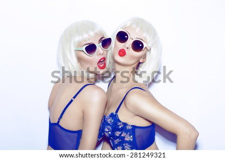 Closeup fashion lifestyle portrait of two pretty best friends girls,wearing bright swag style bra,sunglasses,having fun and make crazy funny faces.Two sisters posing with red lips.Hipster.Swag style. - stock photo