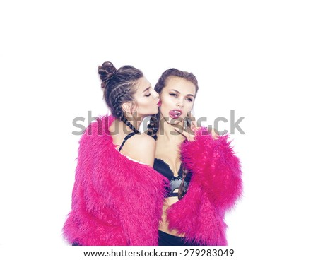 Closeup fashion lifestyle portrait of two pretty best friends girls,wearing bright swag style pink fur,jewelry,having fun and make crazy funny faces.Two sisters posing on party.Hipster.Swag style.