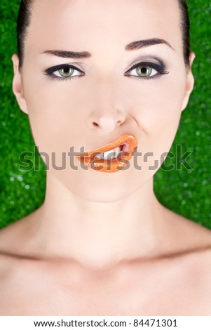 Closeup fashion portrait of a woman pulling a strange face isolated on green - stock photo