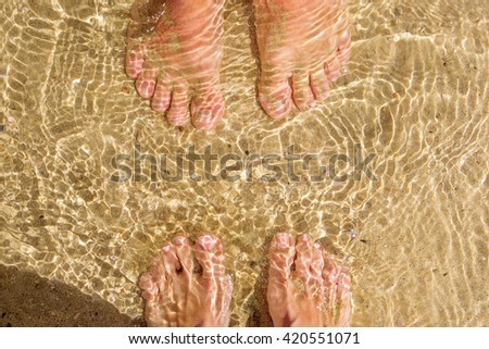 Closeup feet of man and woman in the sea. Top view. Summer vacation concept - stock photo