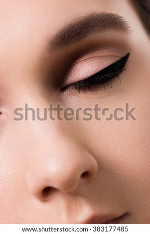 closeup female eyes with long eyelashes and black eyeliners