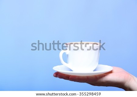 Closeup female hand holding a cup of latte coffee cappuccino hot drink in autumn winter time copyspace blue background - stock photo