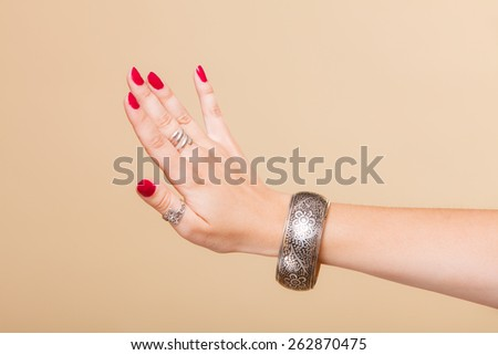 Closeup female hand, woman showing fashionable accessories bijouterie armlet and rings on finger. Beauty red nails. - stock photo