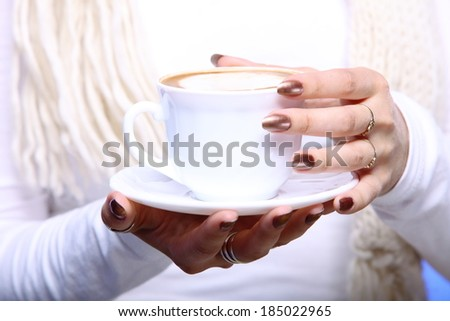 Closeup female hands holding a cup of latte coffee cappuccino hot drink in winter time blue background - stock photo