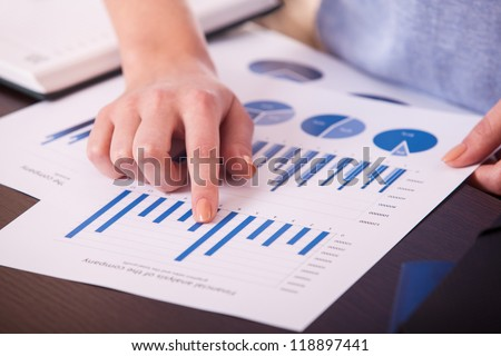 closeup female hands over business document with graph and chart - stock photo