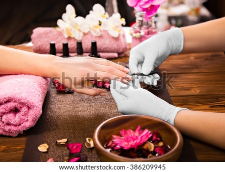 Closeup finger nail care by manicure specialist in beauty salon.  - stock photo